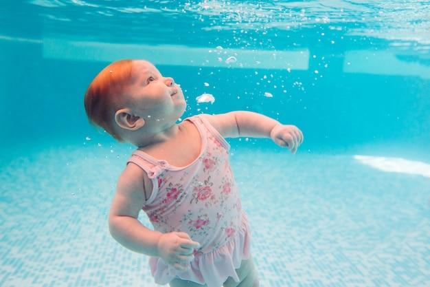 Baby. gelukkig kind leren zwemmen, duiken onder water met plezier in het zwembad om fit te blijven. duiken.