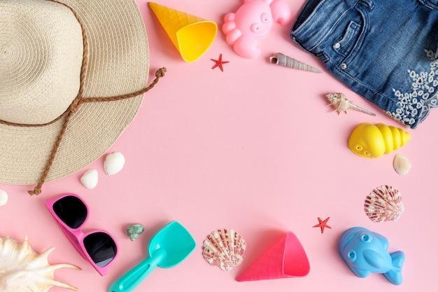 Baby girl's accessoires voor op het strand. strohoed, zonnebril, zandvormen, shorts, badpak, cockleshells op een roze achtergrond. uitzicht van boven.