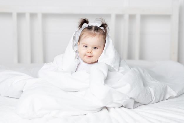 Baby gluren uit onder de deken op het bed thuis, het concept van een gelukkige liefdevolle familie en kinderen
