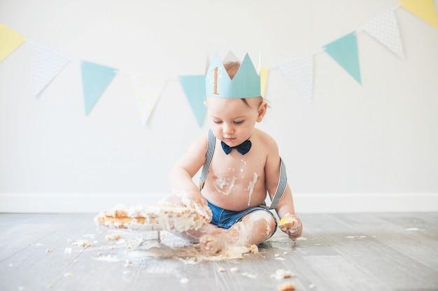 Baby het spelen met een cake tijdens zijn de verjaardagspartij van de smashcake
