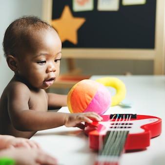 Baby het spelen met een stuk speelgoed gitaar