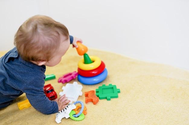 Baby het spelen met kleurrijk speelgoed thuis. vroege ontwikkeling voor kinderen.