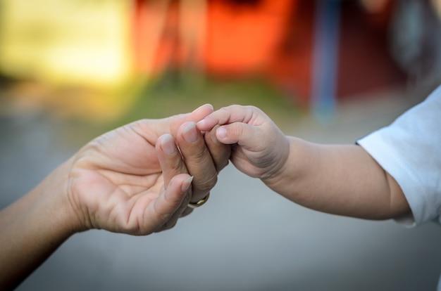 Baby houdt de hand van zijn moeder vast, moeder en dochter houden hun handen vast.