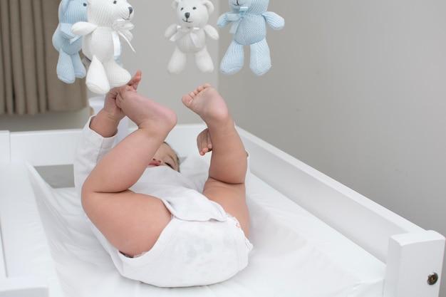 Baby houdt zijn voet vast terwijl hij op de commode ligt