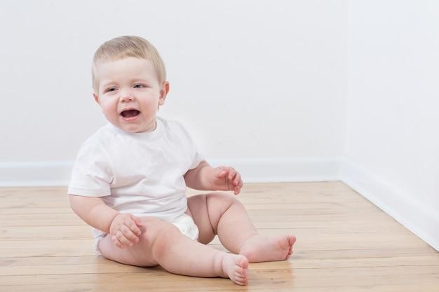 Baby huilen zittend op een houten vloer