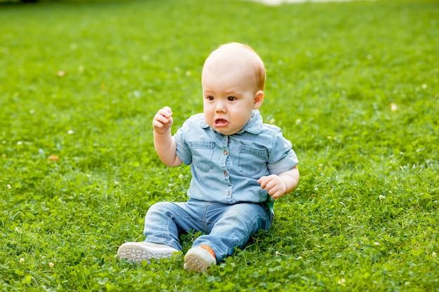 Baby huilen zittend op het gazon