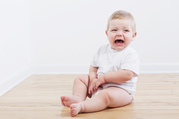 Baby huilende zittend op houten vloer