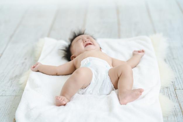 Baby huilt in een luier op de grond