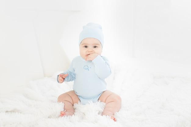 Baby in blauwe kleren, zittend op een wit tapijt thuis