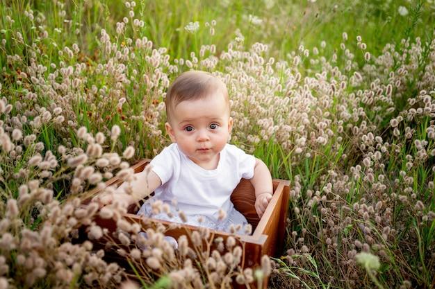 Baby in bloemen op het veld in de zomer in een witte jurk