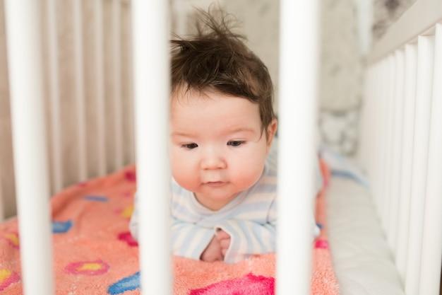 Baby in de wieg. grappige baby in een wit hemelbed. kinderkamer interieur en beddengoed voor kinderen