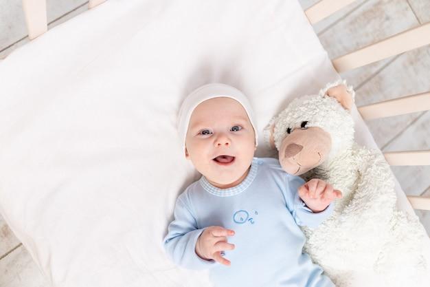 Baby in de wieg, portret van een glimlachende baby 3 maanden in de wieg met een teddybeer speelgoed, kinderen en geboorte concept