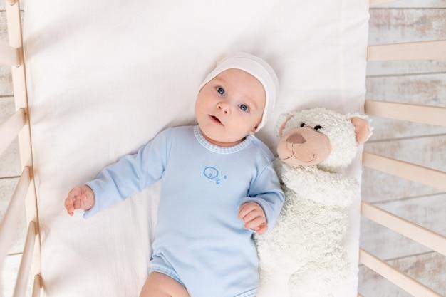 Baby in de wieg, portret van een schattige baby 3 maanden in de wieg met een teddybeer speelgoed, kinderen en geboorteconcept