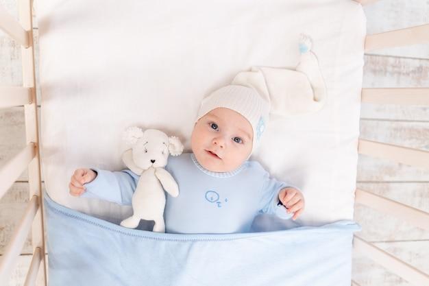 Baby in de wieg 's ochtends thuis of voor het slapengaan, portret, familie- en geboorteconcept Premium Foto
