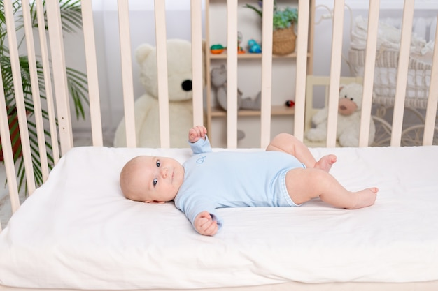 Baby in de wieg, schattige kleine jongen van zes maanden liggend in de kinderkamer op het bed