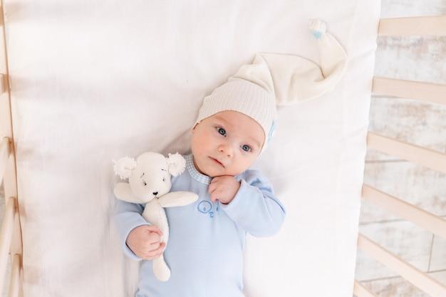 Baby in de wieg thuis in de ochtend of voor het naar bed gaan, portret, familie en geboorteconcept