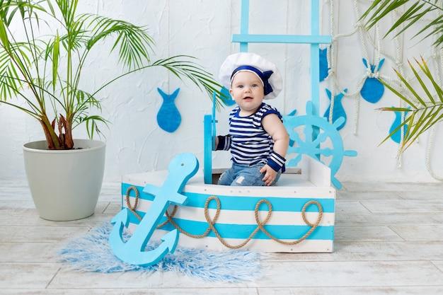 Baby in de zeezone in een boot en een matrozenvest, het concept van reizen en recreatie