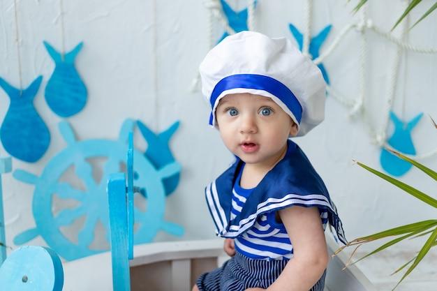 Baby in de zeezone met een schip in een matrozenvest, het concept van zomervakantie