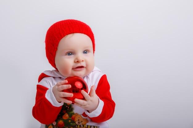 Baby in een kerstkabouterkostuum met een kerstbol