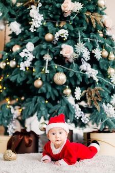 Baby in een kerstman kostuum liggend op een buik in de buurt van de kerstboom en cadeautjes