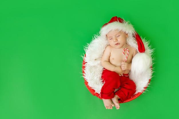 Baby in een kerstman kostuum liggend op een groene achtergrond