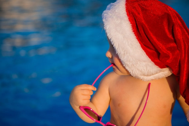 Baby in een kerstmuts en zonnebril in het zwembad