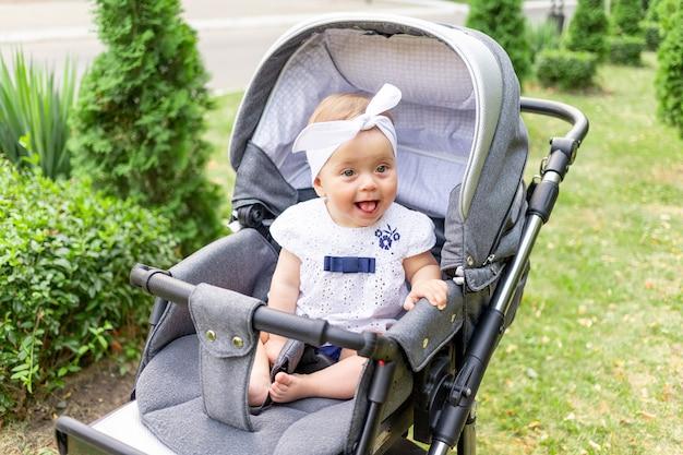 Baby in een kinderwagen loopt in de zomer in witte kleren