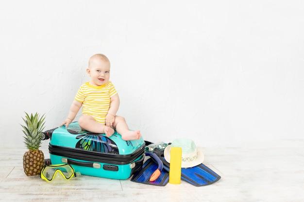 Baby in een koffer met zomerdingen voor vakantie, reizen en zomerconcept, kopieer ruimte