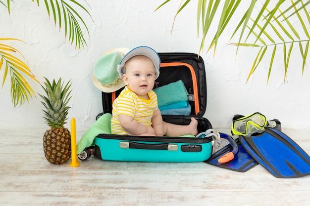 Baby in een koffer met zomerspullen voor vakantie, reizen en zomerconcept