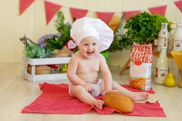 Baby in een koksmuts met eten om hem heen