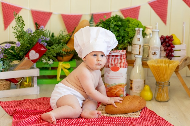 Baby in een koksmuts zit met bloem en groenten