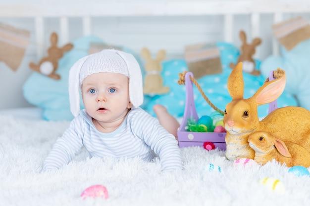 Baby in een konijnenhoed op een bed met paaseieren en konijnen, vrolijk pasen-concept