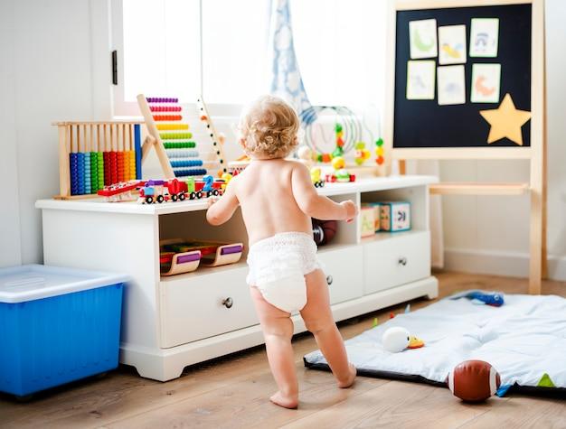 Baby in een luier in een speelkamer