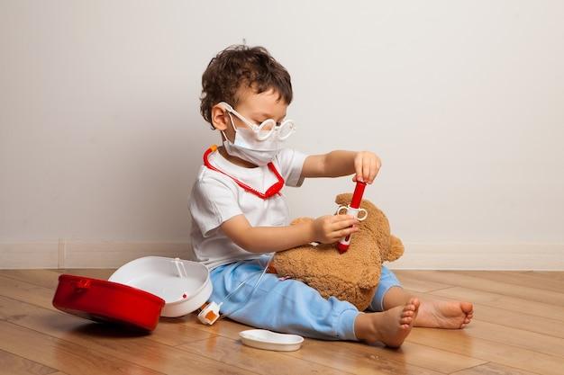 Baby in een medisch masker speelt met een teddybeer babyjongen in een masker zet een masker op een virusbeschermingstraining voor speelgoed
