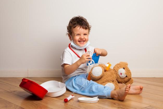 Baby in een medisch masker speelt met een teddybeer. babyjongen in een masker zet speelgoed op een masker. virusbeschermingstraining.