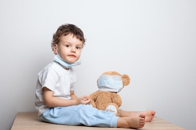 Baby in een medisch masker speelt met een teddybeer. babyjongen in een masker zet speelgoed op een masker.