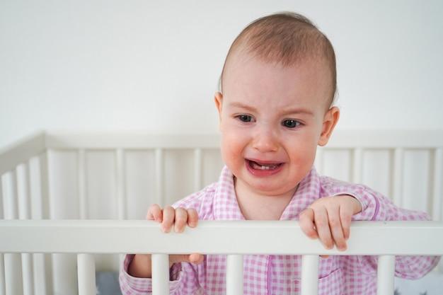 Baby in een prachtige roze geruite pyjama. het kind werd wakker en huilde veel. een kind staat in zijn witte wieg.