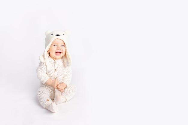 Baby in een warm pak en een berenhoed op een witte geïsoleerde achtergrond, ruimte voor tekst