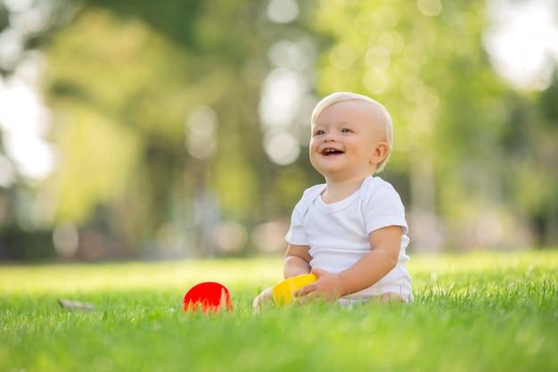 Baby in een witte romperzitting op het groene gras spelen
