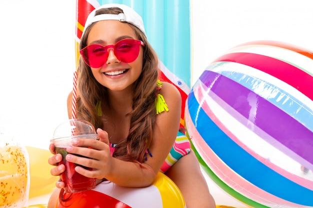Baby in een zwempak met een brede glimlach op zijn gezicht, het concept van de de zomervakantie, geïsoleerde witte achtergrond