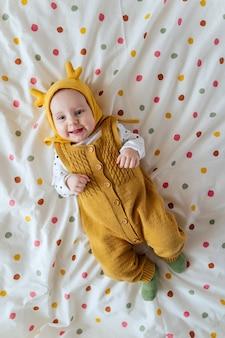 Baby in gebreide stijlvolle kleding en grappige hoed glimlachend en lachend op bed thuis. mode kindje. gelukkige jeugd.