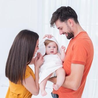 Baby in handdoek gehouden door ouders