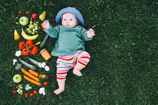 Baby in kleurrijke kleding die voedsel en frame van verschillende verse fruitgroenten op groen gras probeert