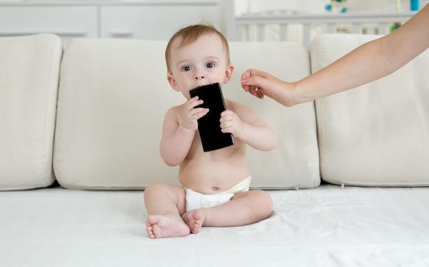 Baby in luiers die op bed zit en smartphone vasthoudt
