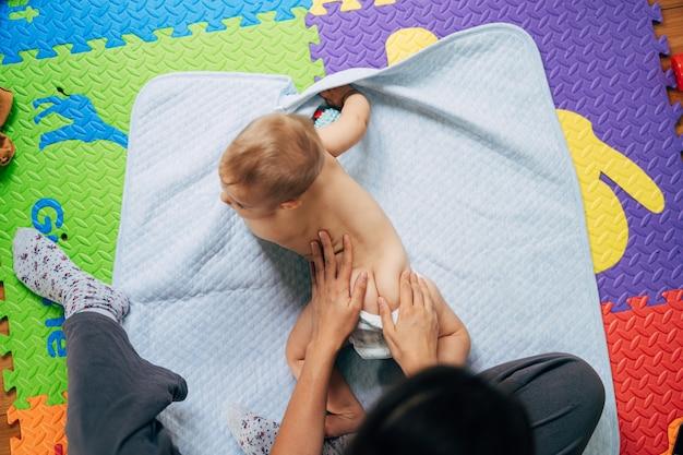 Baby in luiers ligt op zijn buik op een blauwe deken over een gekleurd kleed op de vloer