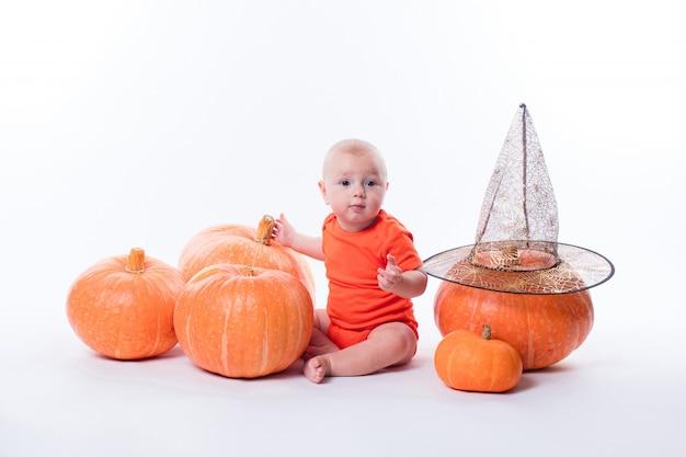 Baby in oranje t-shirtzitting op een witte omringde muur