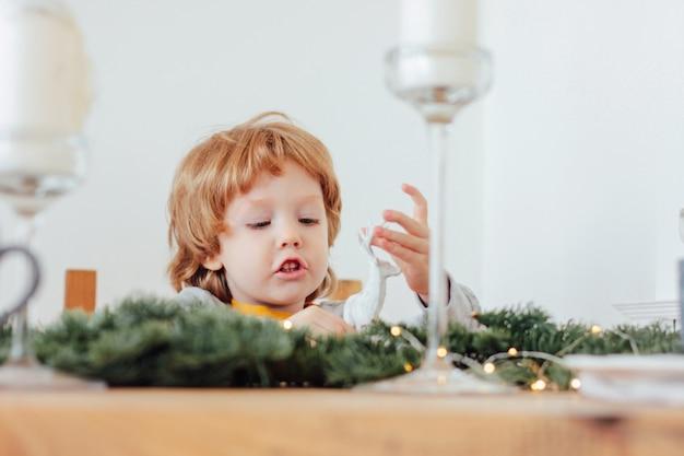 Baby in pyjama's die kerstmisstuk speelgoed herten, feestelijke lijst houden