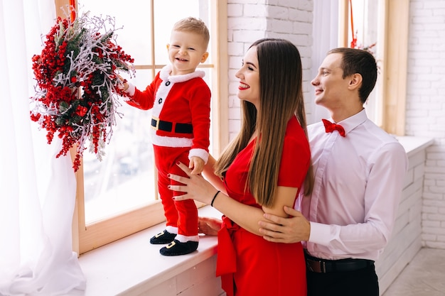 Baby in santakostuum op vensterbankouders in feestelijke kleren dichtbij venster en baby. kerst krans.
