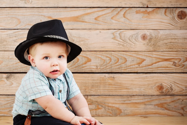 Baby in zwarte hoed, shirt en bretels shorts op houten achtergrond