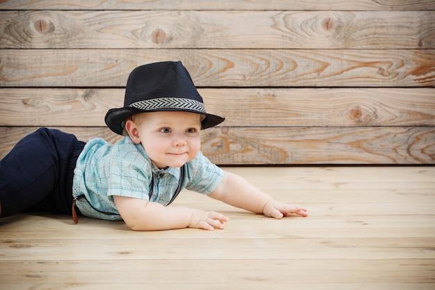 Baby in zwarte hoed, shirt en korte broek met bretels op hout